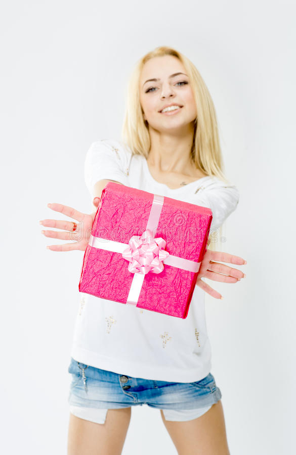 Barn gladlynt flicka som rymmer en gåva, på vit backgroun arkivbild