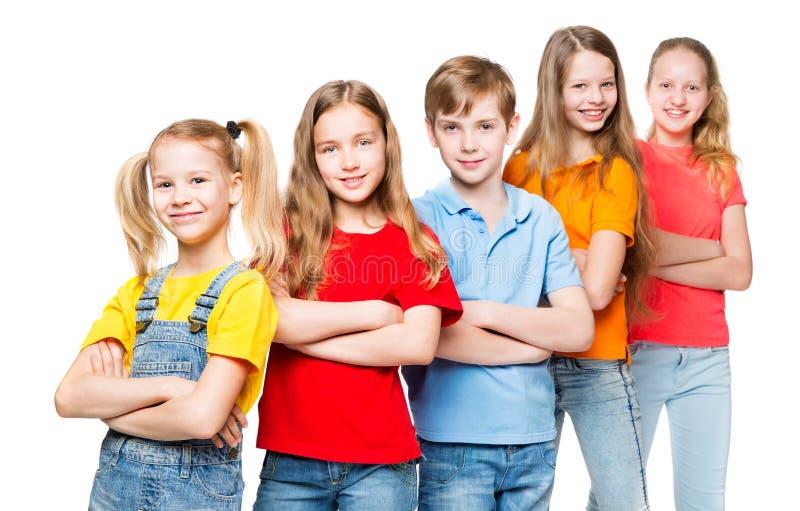 Barn grupp, ungar på vitt lyckligt Smilling folk i färgrika t-skjortor royaltyfria foton