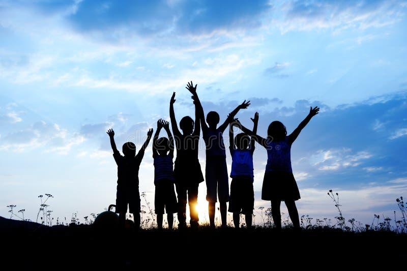 barn grupperar den lyckliga silhouetten royaltyfria foton