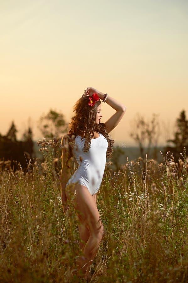 Barn härlig attraktiv modell i baddräkten som poserar i ett fält arkivfoton