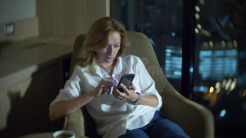 Barn härlig blond kvinna som använder en smartphone, på en stol i ett rum med panorama- förbise för fönster fotografering för bildbyråer