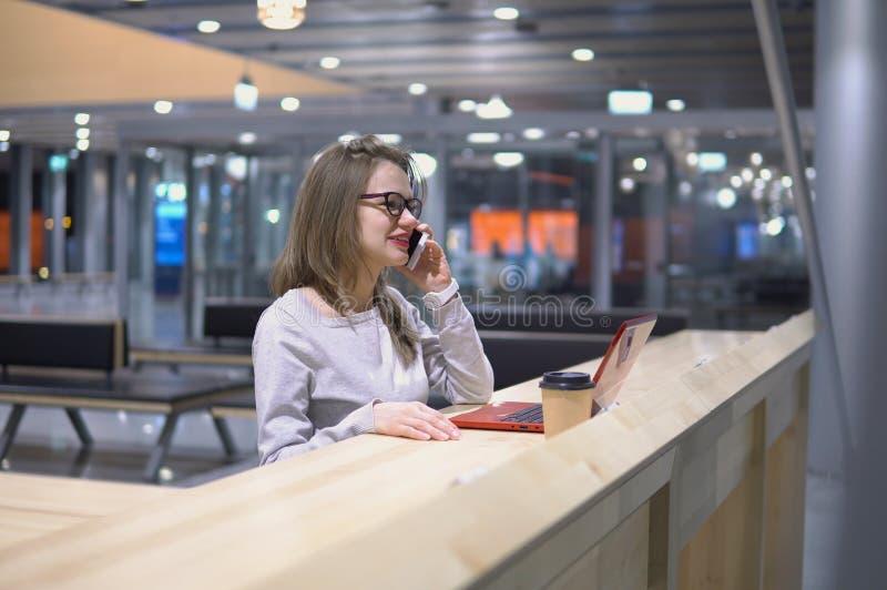 Barn, härlig flicka som talar på telefonanseendet på en tabell med en bärbar dator, och en kopp kaffe på flygplatsen royaltyfria foton