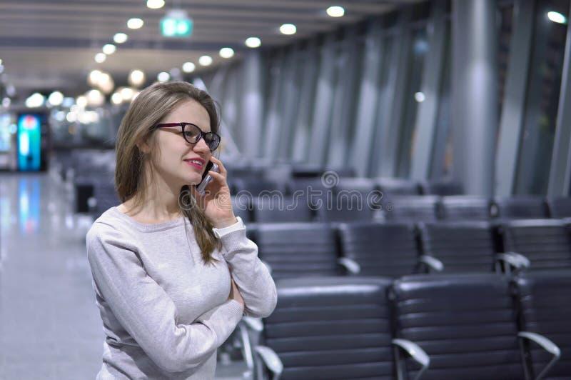 Barn härlig flicka som talar på telefonen i en tom flygplatsterminal royaltyfria foton