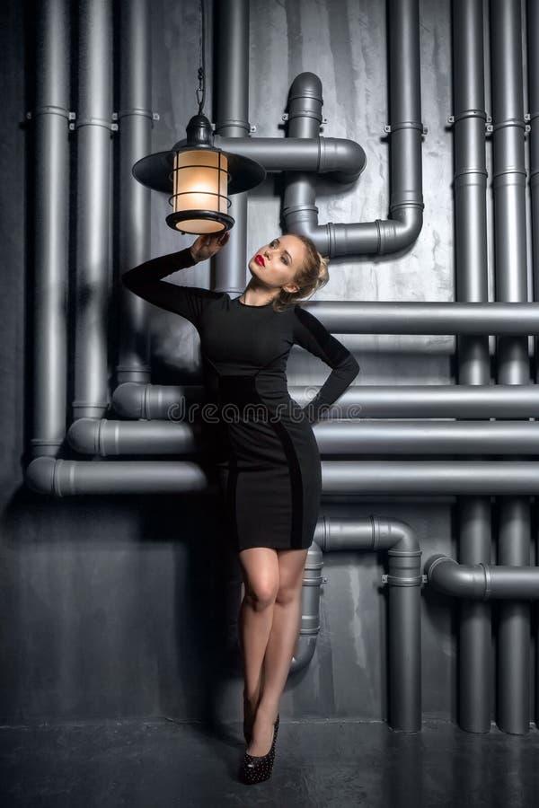 Barn härlig kvinna i den svarta klänningen som rymmer två retro lampor royaltyfria bilder