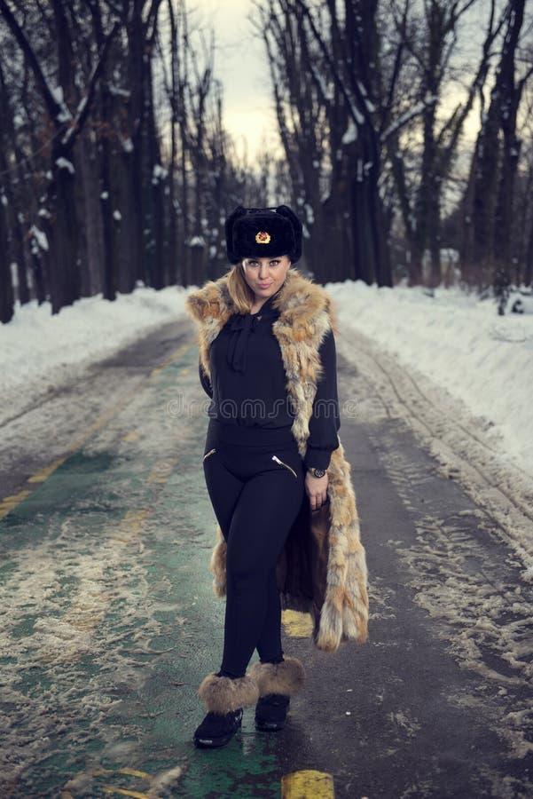 Barn härlig kvinna som blåser snow in mot kamera på vinterbakgrund royaltyfri fotografi