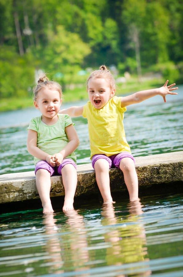 Barn har gyckel på sjön royaltyfri foto