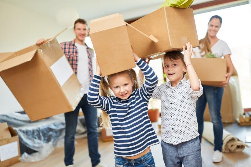 Barn hjälper föräldrarna med flyttningen arkivfoto