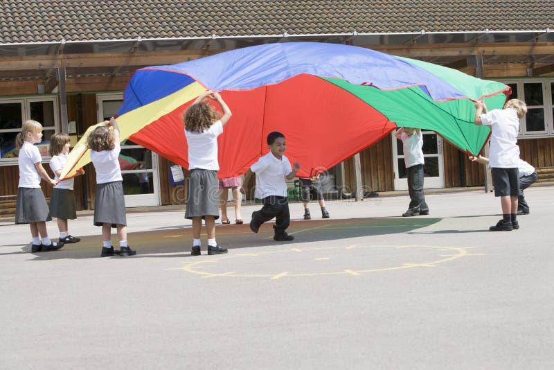 barn hoppa fallskärm leka barn arkivfoto