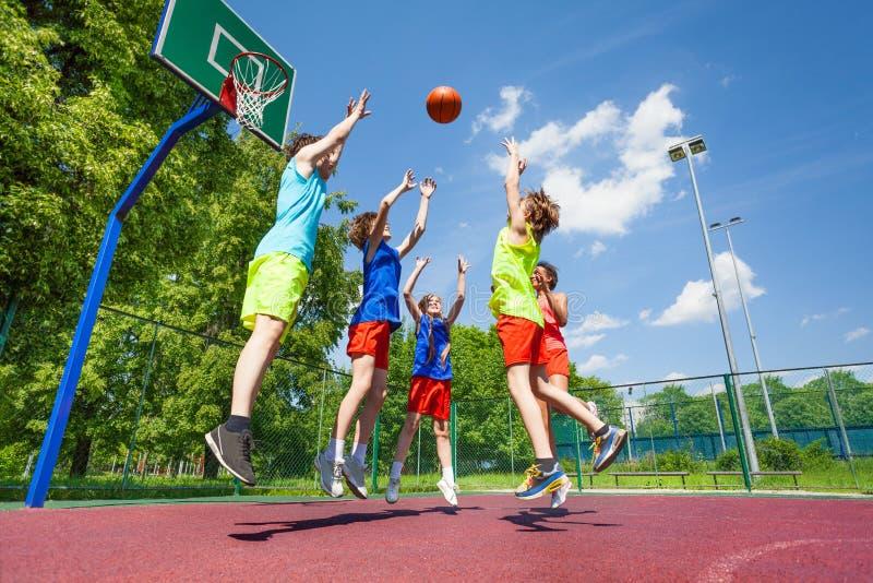 Barn hoppar för att flyga bollen under basket arkivfoton