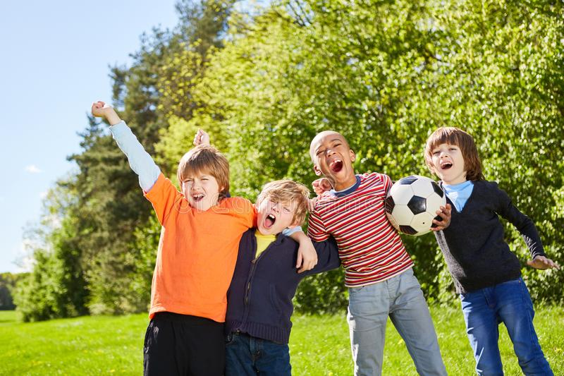 Barn hurrar som vänner och fotbollslaget arkivbild
