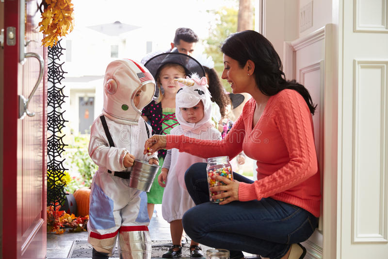 Barn i allhelgonaafton kostymerar trick eller behandling royaltyfri foto