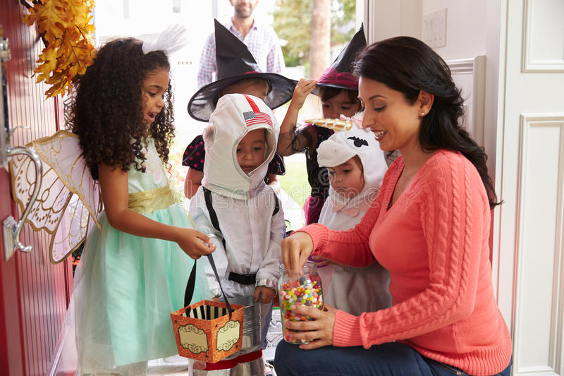 Barn i allhelgonaafton kostymerar trick eller behandling royaltyfri fotografi
