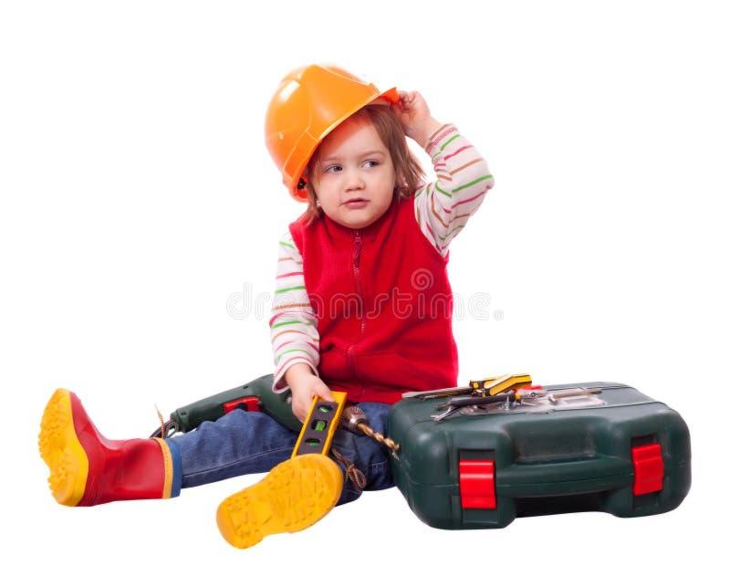 Barn i byggmästarehardhat med funktionsdugliga hjälpmedel royaltyfri bild