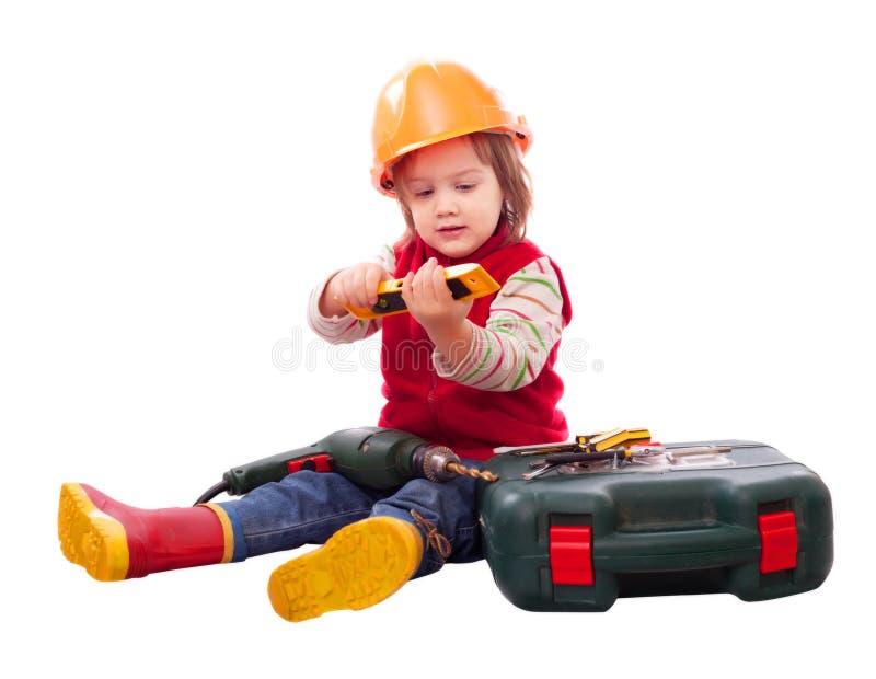 Barn i byggmästarehardhat med hjälpmedel royaltyfria foton