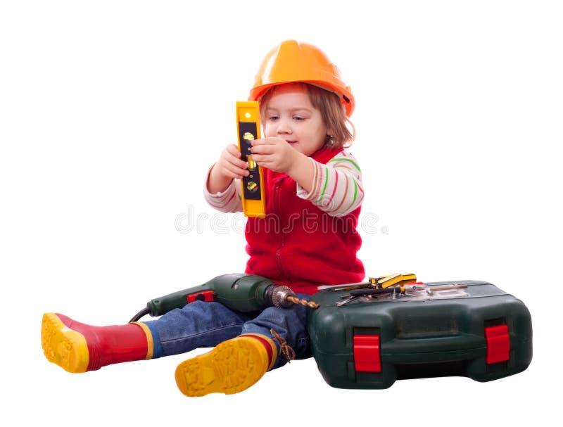 Barn i byggmästarehardhat med hjälpmedel royaltyfri foto
