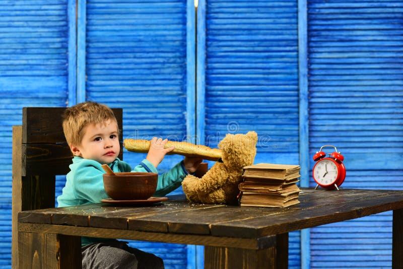 Barn i dagis Det lilla barnet äter den franska bagetten Barnet tycker om smakligt matställesammanträde på tabellen Smaklig mat fö arkivfoton