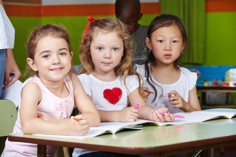 Barn i dagis med pennor royaltyfri bild