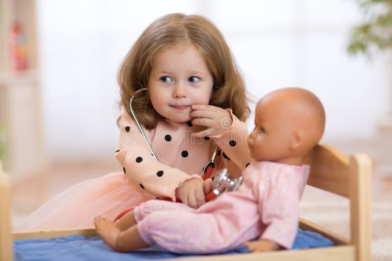 Barn i dagis Unge i daghem Liten flickaförskolebarn som spelar doktorn med dockan fotografering för bildbyråer