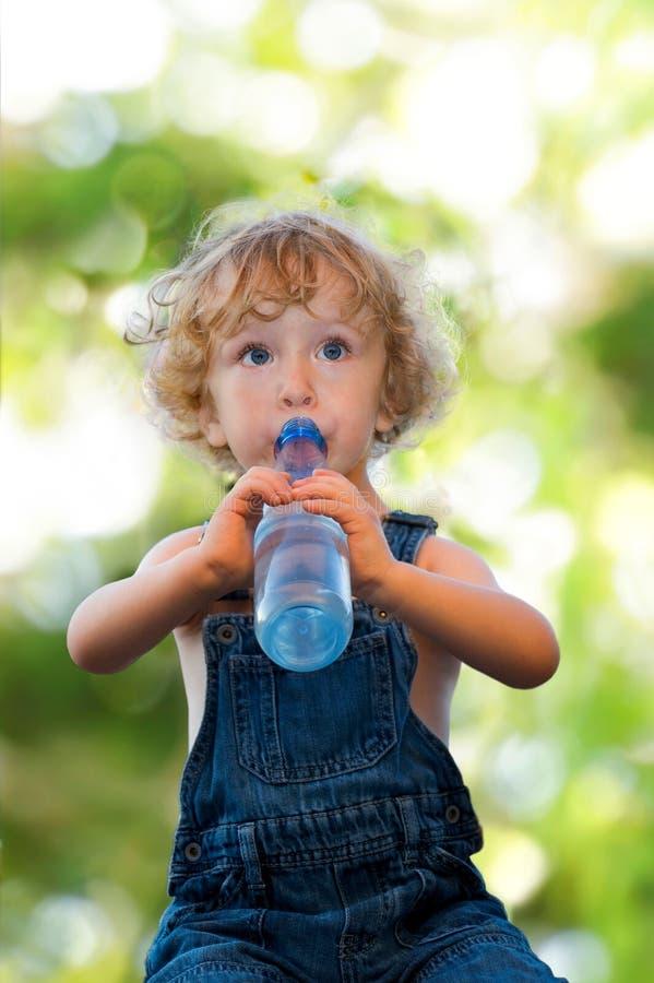 Barn i denimdräktdricksvatten fotografering för bildbyråer