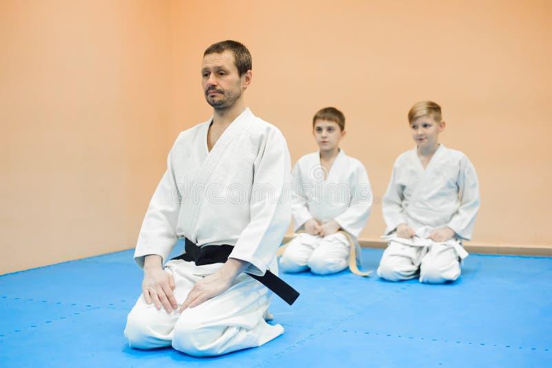 Barn i en kimono sitter på tatamien med en lagledare på ett seminarium på kampsporter royaltyfria bilder