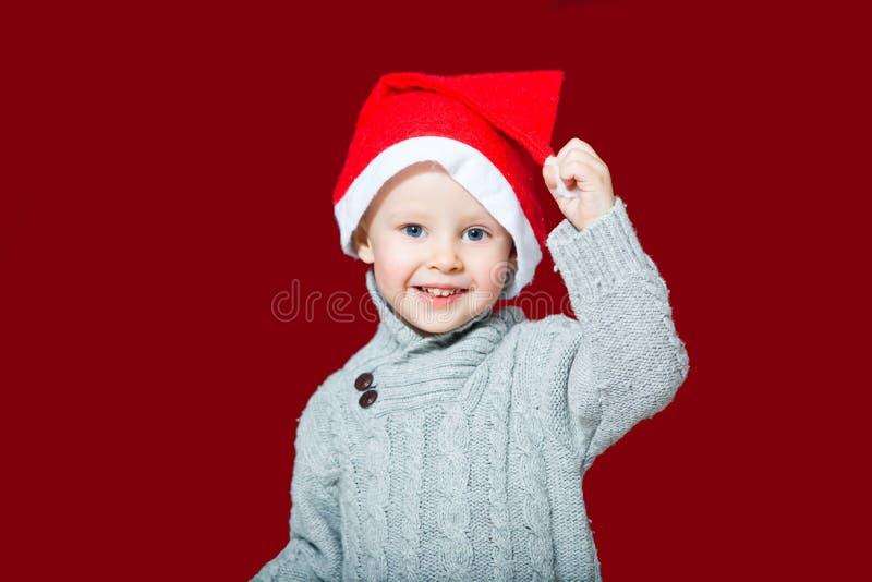 Barn i en röd Santa Claus hatt arkivfoton