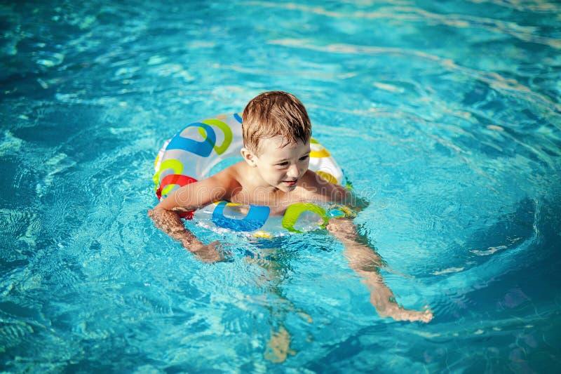 Barn i en simbassäng som har hans första badkurser arkivfoto