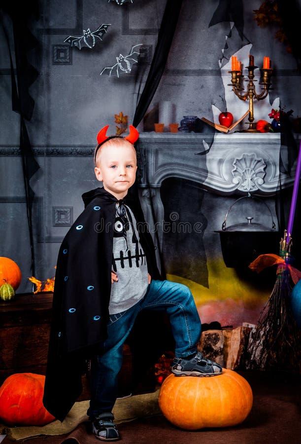 Barn i en svart kappa på festmåltiden av allhelgonaaftonen arkivfoton