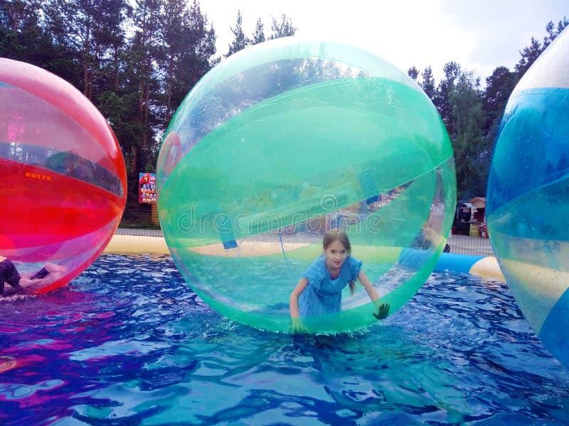 Barn i en vattenballong fotografering för bildbyråer