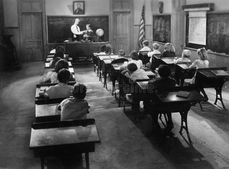 Barn i ett grupprum med en lärare (alla visade personer inte är längre uppehälle, och inget gods finns Leverantörgarantitha arkivbild