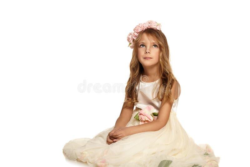 Barn i ett klänningsammanträde på golvet royaltyfri fotografi