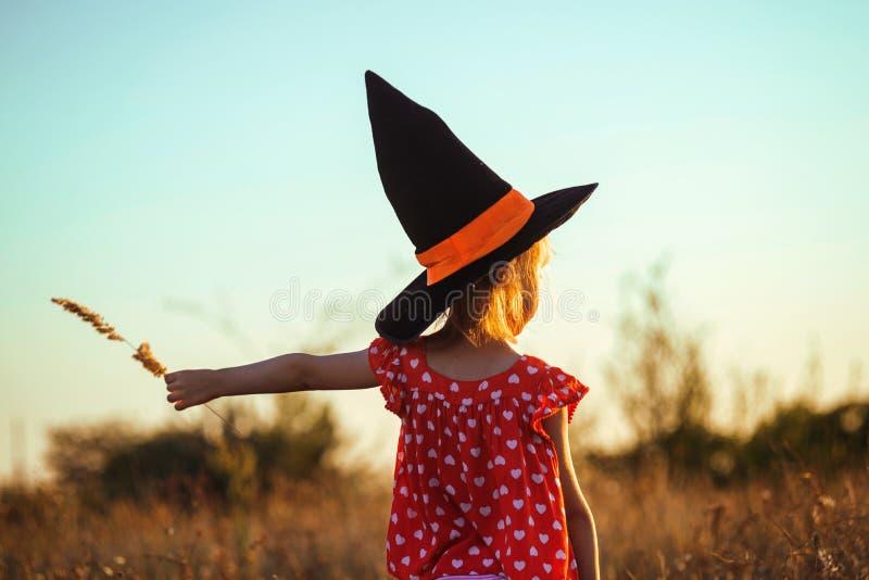 Barn i häxahattdet fria, bakre sikt, vykort för höstferieallhelgonaaftonen fotografering för bildbyråer