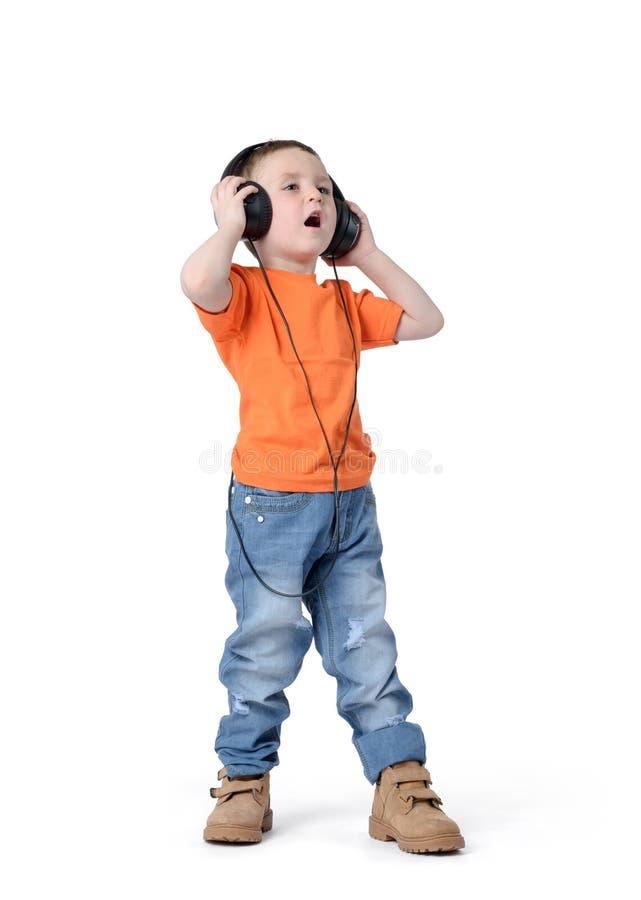 Barn i hörlurar på en vit bakgrund fotografering för bildbyråer