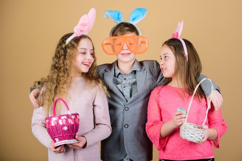 Barn i kaninkaninöron lyckliga easter Vårferieparti Äggjakt Familj och systerskap Små flickor och pojke royaltyfria foton
