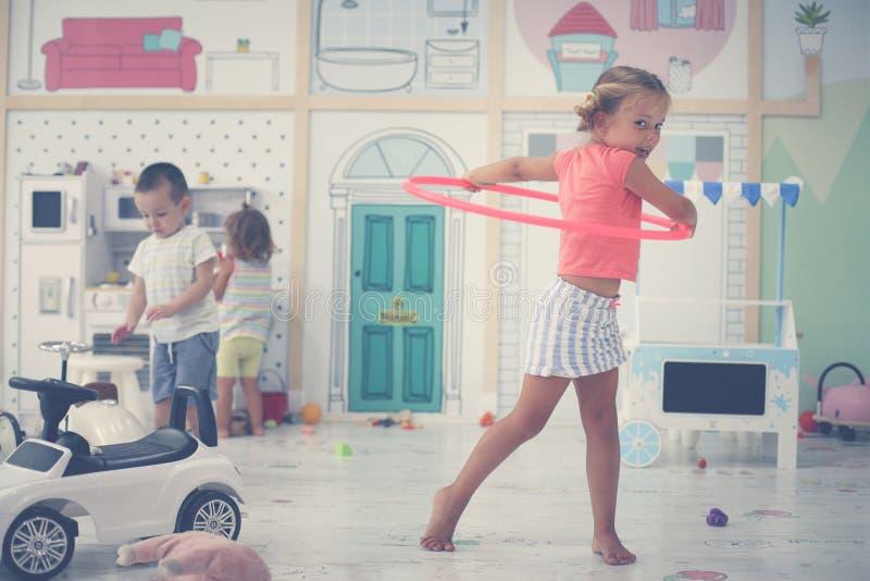 Barn i lekrum Den förskole- flickan spelar med hoolahope royaltyfri bild