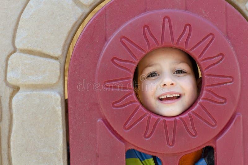 Barn i lekstugafönster royaltyfria bilder