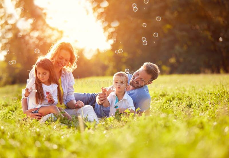 Barn i natur gör såpbubblor arkivbild