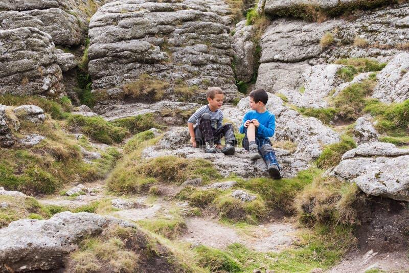 Barn i naturen, sammanträde eller vaggar royaltyfri bild