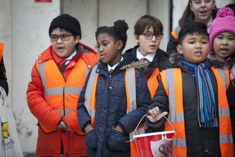 Barn i orange waistcoats sjunger julsånger, mot efterkrav pengar för välgörenhet arkivfoto