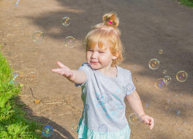 Barn i parkera som jagar såpbubblor arkivfoto