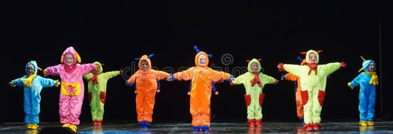 Barn i roliga kulöra overallfrämlingar som dansar på etapp royaltyfria bilder