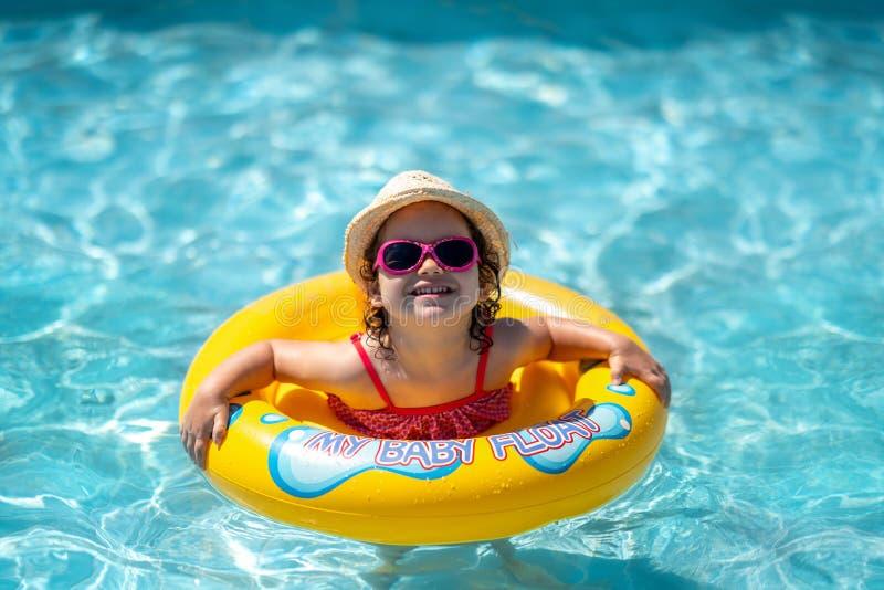 Barn i simbassäng med cirkeln Sommarsemester med ungar arkivfoton