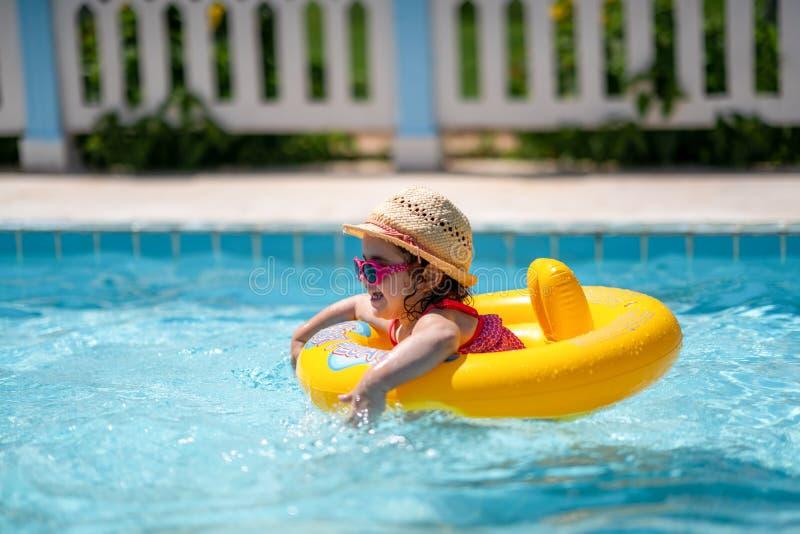 Barn i simbassäng med cirkeln Sommarsemester med ungar royaltyfria foton