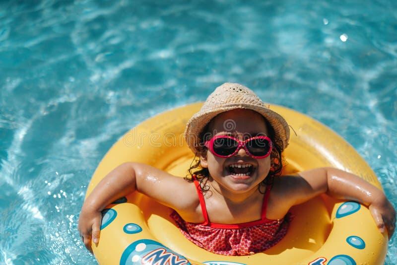 Barn i simbassäng med cirkeln Sommarsemester med ungar arkivbilder