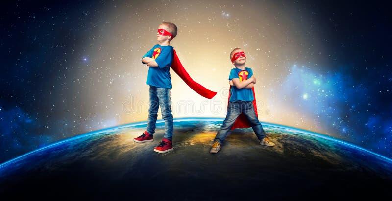 Barn i superherodräkter bevakar planeten royaltyfri fotografi