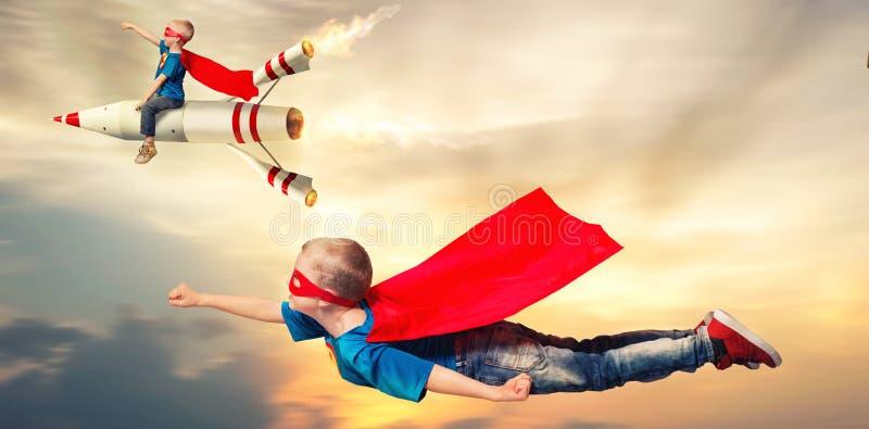 Barn i superherodräkter flyger och visar toppna kapaciteter arkivbild