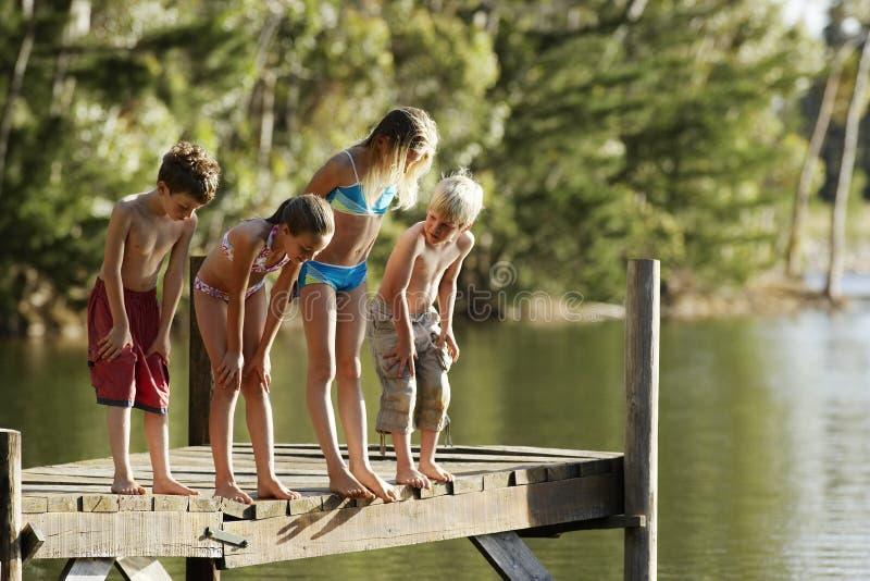 Barn i Swimwearanseende på bryggan vid sjön fotografering för bildbyråer