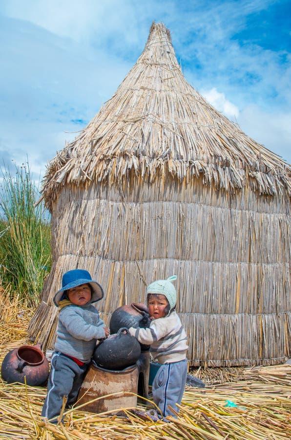 Barn i traditionell by på sjön Titicaca i Peru arkivfoto