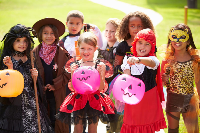 Barn, i trick eller behandling för utsmyckad dräktklänning gående royaltyfria bilder