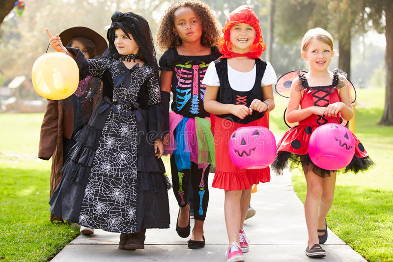 Barn, i trick eller behandling för utsmyckad dräktklänning gående arkivfoton