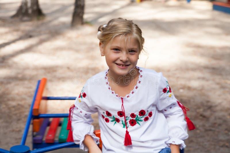 Barn i ukrainsk stilskjorta på en swing royaltyfria bilder